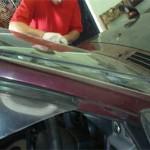 Мастер аккуратно снимает молдинги лобового стекла специнструментом.