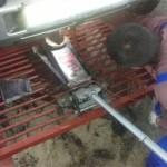 Сергей домкратит мотор и отворачивает гайки старой левой подушки двигателя.