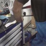 Сергей отпиливает от полосы готовый новый кронштейн радиатора