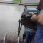 Сергей разворачивает отверстие в дюралевой полосе для нового кронштейна, отметив диаметр демпфера