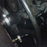 Вид на установленный нижний патрубок нового радиатора и шланг охлаждения автомата с новыми хомутами