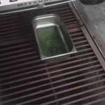 Антифриз сливается из старого радиатора в судок после открытия сливного крана