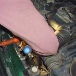 Мастер Сергей с магнитом и лампой просовывает правый нижний болт помпы под кожух ГРМ перед затяжкой